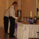 Goście przy stole z fontanną serową i wędlinami