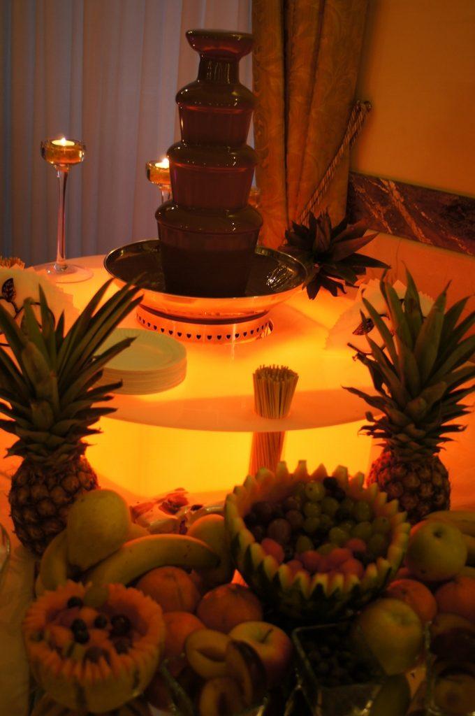 Owocowe dekoracje na lustrzanej tacy i fontanna czekolady
